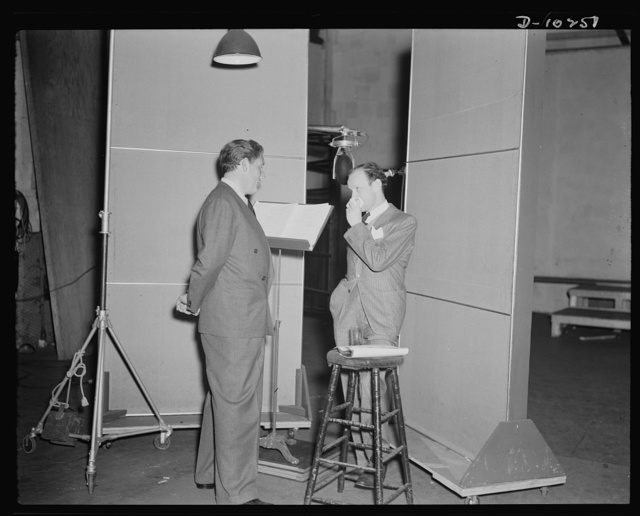 """Spencer Tracy, narrator and Garson Kanin, director, at the Long Island Studios of the Army Signal Corps for the recording of Spencer Tracy's narration of the """"Ring of Steel,"""" an Office of Emergency Management film (OEM), on February 19th, 1942"""