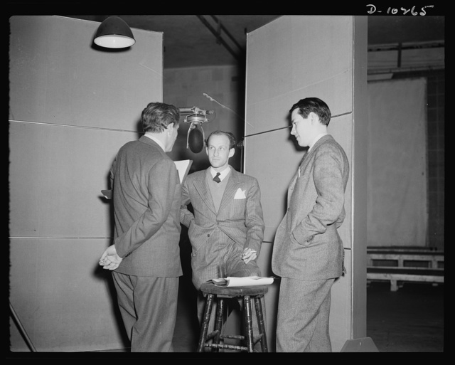 """Spencer Tracy, narrator, Garson Kanin, director, Wallace Russell, writer, at the Long Island Studios of the Army Signal Corps for the recording of Spencer Tracy's narration fo the """"Ring of Steel,"""" and Office of Emergency Management (OEM) film, on February 19, 1942"""