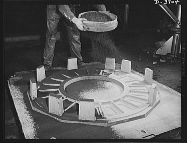 Sprinkling sand on the face of a mold before applying flask. Another step in the long and intricate process of producing aluminum parts for use by Uncle Sam's mechanized forces. Aluminum Industries
