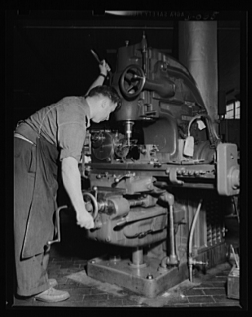 Squaring part of a torpedo. Skilled machine operator working on the process of torpedo manufacture in an eastern Navy arsenal