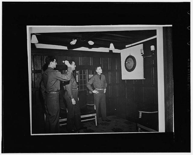 Stratford upon Avon, England. American servicemen practicing at a traditional dart board in an old hotel, the White Swan, taken over by the American Red Cross. Left to right: Private First Class Michael Ryan, of Edgewood, Pennsylvania; Private First Class Paul Smith, of Philadelphia, Pennsylvania; and Private Matthew Stampfl, of Pittsburgh
