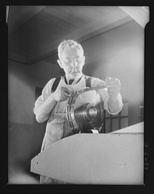 Subcontracting. Passaic home workshop pool. A worker in the Passaic, New Jersey shop of the Howe Machinery Company files a flange used in an expanding mandrel for v-belt drives. In addition to the work in its own shop, the concern is also farming out considerable work through a home workshop pool it organizes