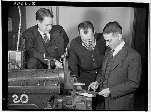Subcontracting. Passaic home workshop pool. Executives of the Howe Machinery Company, Passaic, New Jersey, discuss details of the production of essential Army equipment with a home workshop owner who is a member of the subcontracting pool organized by the company. Left, Mr. Stanley Carlson, President; right, Mr. George Bodganffy, Vice President of Howe Machinery Company. In the center is Mr. John Lindstrom, subcontractor