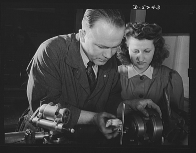 Subcontracting. Passaic home workshop pool. Instructor John Wanelik, of the Howe Machinery Company, Passaic, New Jersey, shows Veronica Stephens how to grind a stripping angle on a cartridge drawing die. A number of young women are being trained for war production jobs in this shop