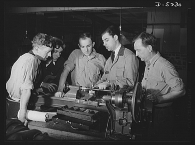 Subcontracting. Passaic home workshop pool. Lathe parts are explained to students in the trade school of the Howe Machinery Company, Passaic, New Jersey. The school trains fifty workers at a time in the production of essential war equipment. More than ninety percent secure jobs after training, some in the Howe shop