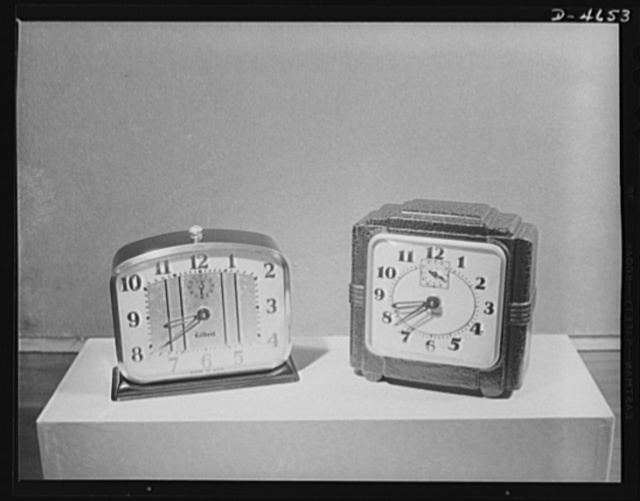 Substitutes. Composition clock cases. New clock conserves critical metals. Two-bit model (right) produced by Gilbert Clock Corporation, compared with metal-case model which sold under the same guarantee. Saves brass, aluminum, phosphor, bronze and steel --and eases the transportation problem by reducing the weight 47 1/2 percent