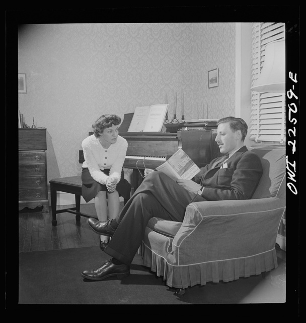 Swedish-American foreman at the SKF roller bearing plant reads to his Italian-American wife at home. Philadelphia, Pennsylvania
