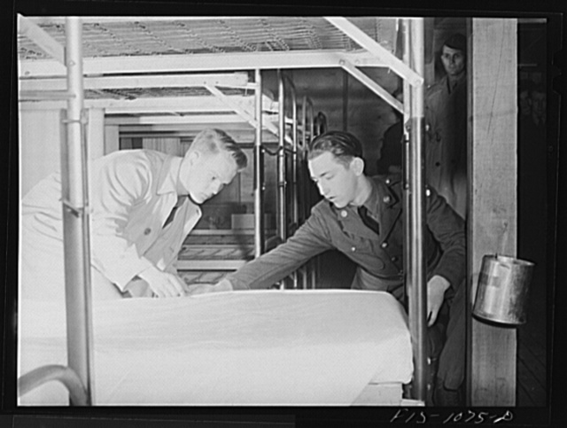 Swedish-American selectee in Minnesota learning how to make a bed as he is inducted into the U.S. Army