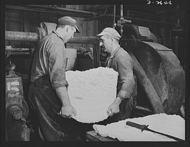 Synthetic rubber (Ameripol). These workers are removing crumbs from the perforated boxes below the coagulating and extractor tanks. The rubber drips into these boxes from the tanks and the water previously added to dissolve the soap in the solution runs off through the perforations in the box. This rubber will now be prepared for the wash mill. Goodrich