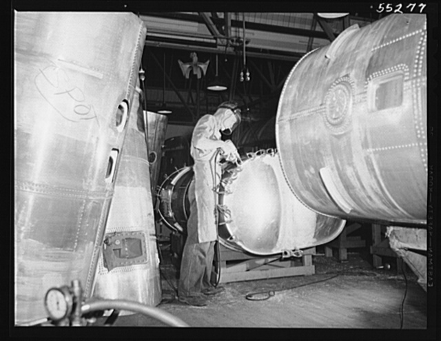 Tanks ready for final assembly surround this North American employee as he finishes another gasoline tank for a B-25 bomber