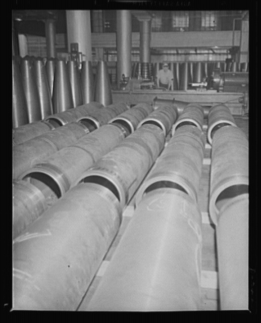 """Teeth for a new destroyer. Partially-completed torpedo air flasks with """"after bodies"""" in the background at an eastern Navy arsenal"""