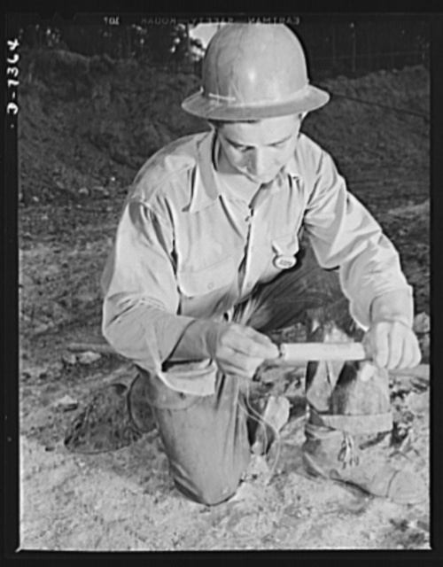 Tennessee Valley Authority. Construction of Douglas Dam. Attaching a fuse to a stick of dynamite for a trim shot at the site of TVA's new Douglas Dam on the French Broad River. This dam will be 161 feet high and 1,682 feet long, with a 31,600 acre reservoir area extending forty-three miles upstream. With a useful storage capacity of approximately 1,330,00 acre feet, this reservoir will make possible the addition of nearly 100,000 kilowatts of continuous power to the TVA system in dry years and almost 170,000 kilowatts in the average year