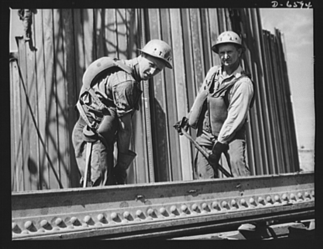 Tennessee Valley Authority power and conservation. Fort Loudoun Dam construction. Placing a structural member for the cofferdam at the new Fort Loudoun Dam, furthest upstream of the TVA's main Tennessee River projects. Scheduled for closure and first storage of water early in 1943, this dam will create a 15,000-acre lake reaching fifty-five miles upstream to the city of Knoxville. The reservoir will have a useful storage capacity of 126,000 acre-feet. Power installation of 64,000 kilowatts is authorized, with a possible ultimate of 96,000 kilowatts. Note safety precautions in the form of life preservers strapped to the backs of these workers