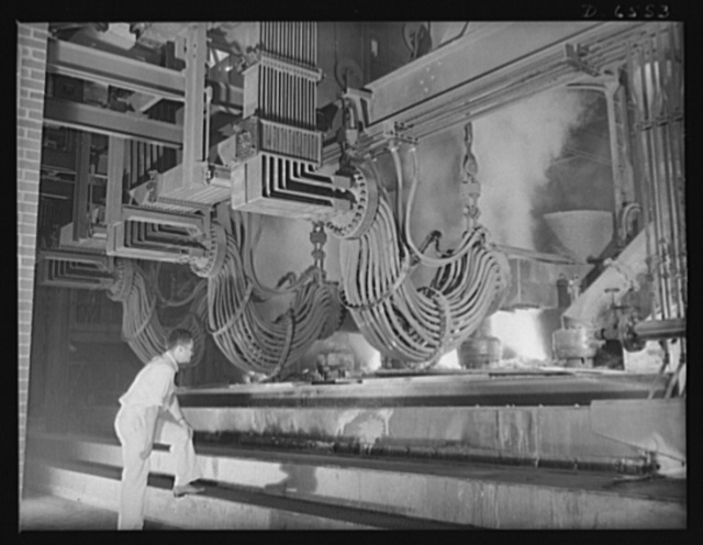 """Tennessee Valley Authority production. Elemental phosphorus. A large electric phosphate smelting furnace used in the making of elemental phosphorus in a TVA chemical plant in the Muscle Shoals area. The phosphorus, used in the manufacture of incendiary bombs and shells and of material for """"smoke,"""" is produced by smelting phosphate rock, coke, and silica together in the electric furnaces and condensing the resulting phosphorus gases. When surplus phosphorus is available, it is converted into highly concentrated phosphatic fertilizer, much of which is shipped abroad under provisions of the Lend-Lease Bill"""