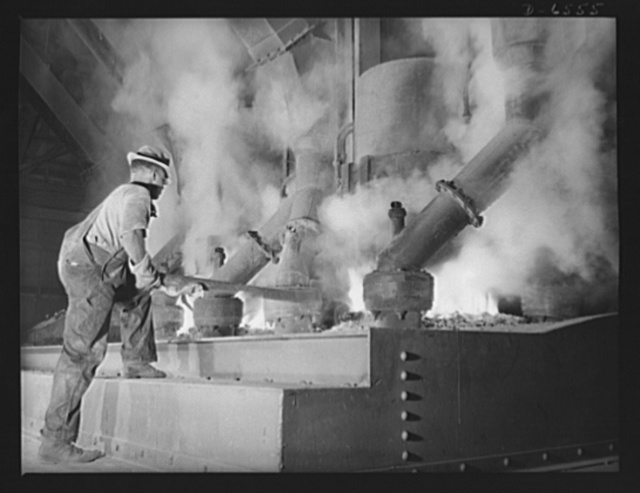 """Tennessee Valley Authority production. Elemental phosphorus. A Negro worker tending an electric phosphate smelting furnace which is producing elemental phosphorus at a TVA chemical plant in the Muscle Shoals area. The phosphorus, used in the manufacture of incendiary bombs and shells and of material for """"smoke,"""" is produced by smelting phosphate rock, coke and silica together in the electric furnaces and condensing the resulting phosphorus gases. When surplus phosphorus is available it is converted into highly concentrated phosphate fertilizer, much of which is shipped abroad under provisions of the Lend-Lease Bill"""