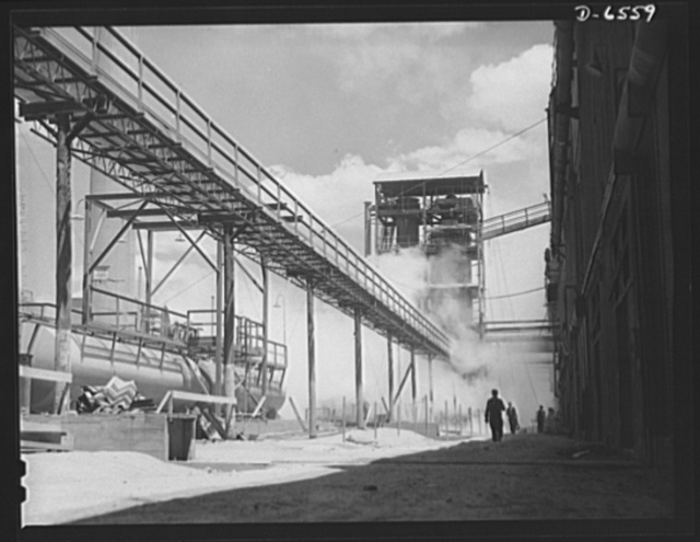 """Tennessee Valley Authority production. Elemental phosphorus. Section of the TVA's phosphoric acid plant operated in conjunction with the making of elemental phosphorus in the Muscle Shoals area. The phosphorus, used in the manufacture of incendiary bombs and shells and of material for """"smoke,"""" is produced by smelting phosphate rock, coke and silica together in electric furnaces and condensing the resulting phosphorus gases. When surplus phosphorus is available it is converted into highly concentrated phosphatic fertilizer, much of which is shipped abroad under provisions of the Lend-Lease Bill"""