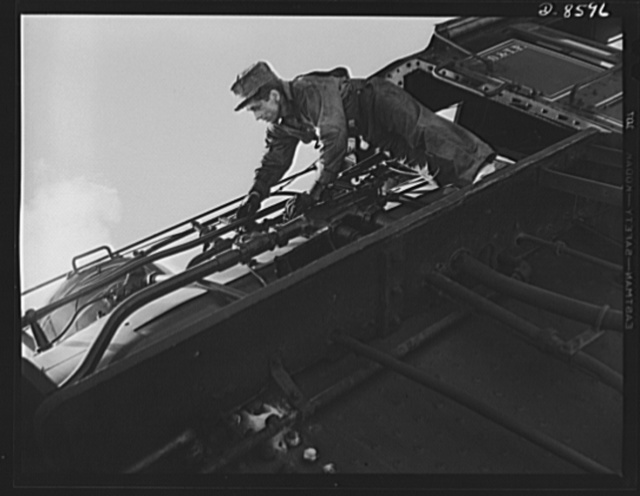 """Tennessee Valley Authority. Railroad crews at Watts Bar Dam. Clearing the sand line is one of the chores that fall to the """"tallow pot,"""" or firemen of a  railway locomotive. In addition jobs like this, the """"tallow pot"""" serves up an average of eight to ten tons of coal each eight hour day to the big """"hog"""" or locomotive. This man fires a train carrying materials for the building of TVA's Watts Bar Dam"""