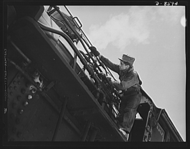 """Tennessee Valley Authority. Railroad crews at Watts Bar Dam. Clearing the sand line is one of the chores that fall to the """"tallow pot,"""" or fireman, of a railway locomotive. In addition to jobs like this, the """"tallow pot"""" serves up an average of eight to ten tons of coal each eight hour day to the big """"hog,"""" or locomotive. This man fires a train carrying materials for the building of TVA's Watts Bar Dam"""