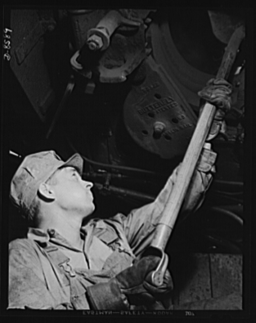 "Tennessee Valley Authority: railroad crews at Watts Bar Dam. The ""tallow pot,"" or fireman, of a freight locomotive carrying materials for the building of the TVA Watts Bar Dam shovels from 16,000 to 20,000 pounds of coal in an eight hour day, in addition to performing other duties around the engine and tender"