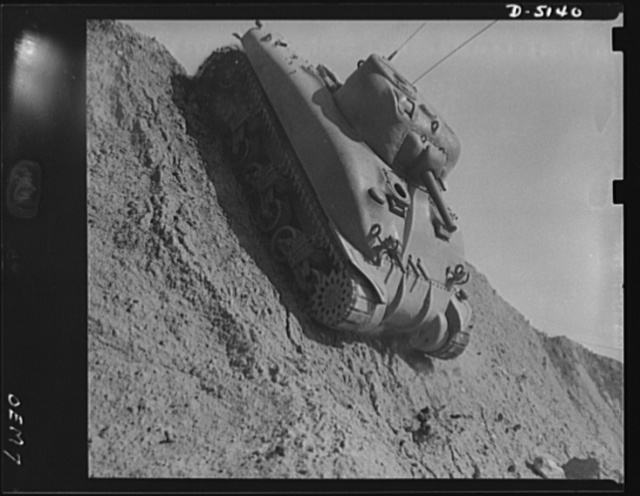 Testing M-4 tanks. Down the steep side of a test hill, as well as up difficult ascents and over many obstacles, a mighty M-4 tank performs brilliantly during the trial runs at an Eastern manufacturing plant