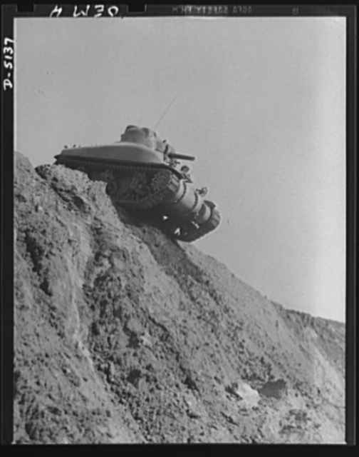 Testing M-4 tanks. Over the top, and ready to go down the steep side of a test hill. A mighty M-4 tank makes successful trial turns at an Eastern manufacturing plant