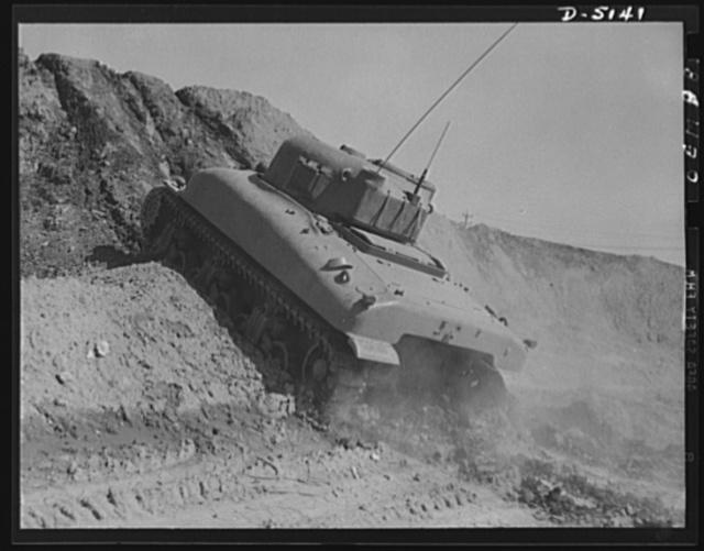 Testing M-4 tanks. Ready to take a stiff grade in loose earth, a mighty M-4 tank performs brilliantly during trial runs at an Eastern manufacturing plant