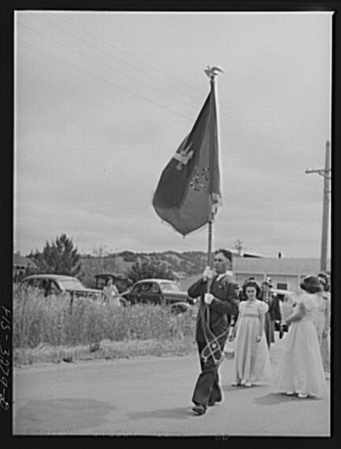 The banner of the I.D.E.S.I. society goes before the Queen and her court in the parade of the Holy Ghost Festival at Novato, California