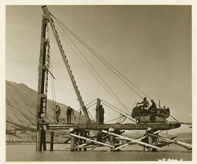 The crash of a pile driver shatters the silence, bulldozers ad caterpillar tractors roar as they carve out a lifeline to our northern bastion. Engineers are shown pounding bridge supports into the riverbed, completing another link