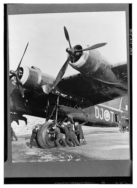 The ground staff pushing a giant Stirling, largest four-engined bomber in the world, out for overhaul. Great Britain?
