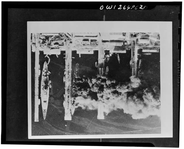 The scuttled French fleet at Toulon: aerial pictures. On November 28, 1942, the day after the scuttling and firing of the ships of the French fleet in Toulon harbor, photographs were taken by the Royal Air Force. Many of the vessels were still burning so that smoke and shadows obscure part of the scene. But the photographs show, besides the burning cruisers, ship after ship of the contre-torpilleurs and destroyer classes lying capsized or sunk, testifying to the thoroughness with which the French seamen carried out their bitter task. While the vast damage done is shown in these photographs, no exact list of the state of the ships can be drawn up, since the ships themselves cannot be seen in an aerial photograph. Thus the upper deck of the battle cruiser Strasbourg is not submerged, but here are signs that the vessel has settled and is grounded. The key  plan C.3296 shows the whereabouts of the majority of the ships and their condition as far as it can be seen from the photographs. Picture shows: damaged and sunk light cruisers and destroyers visible through the shadow and the smoke caused by the burning cruisers