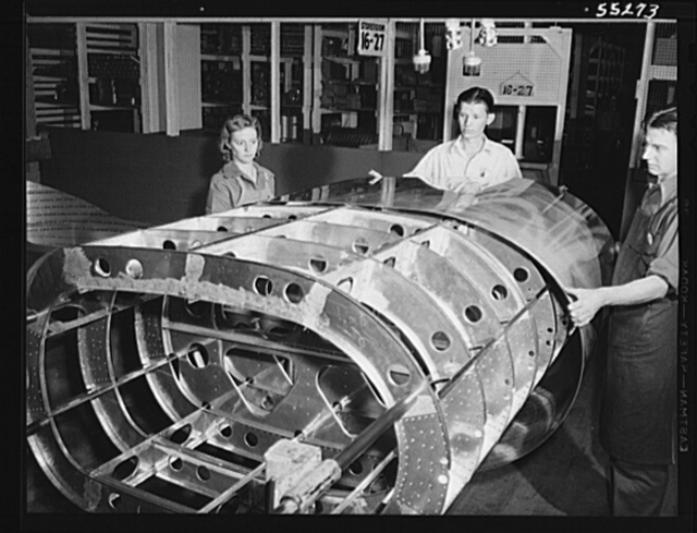 The skin is applied to the frame of a tank for a B-25 bomber. Women can be found in every department at North American Aviation, working together and with men. Next year approximately eighty percent of employees will be women; twenty percent at present