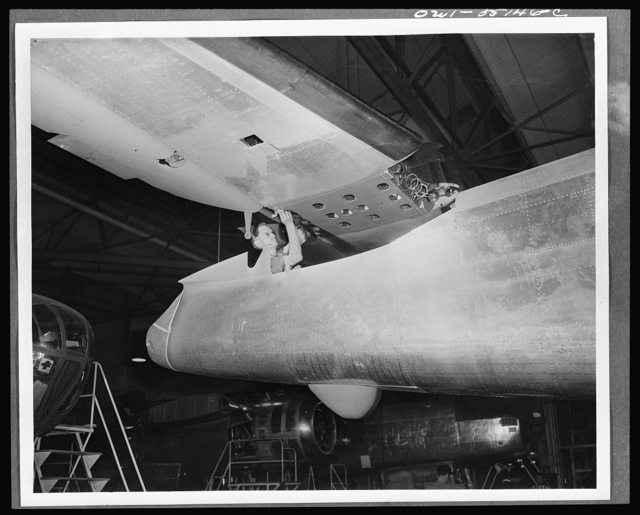 The tail assembly for a North American B-25 bomber is lowered into place from an overhead crane on the final assembly floor