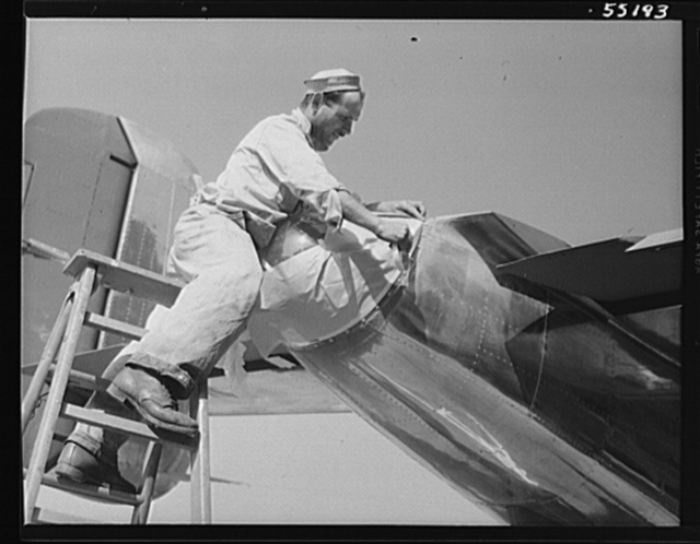 The tail cone of a North American B-25 bomber is masked off by a painter before the ship receives its camouflage. Cone contains tail and signal light. No more gunners