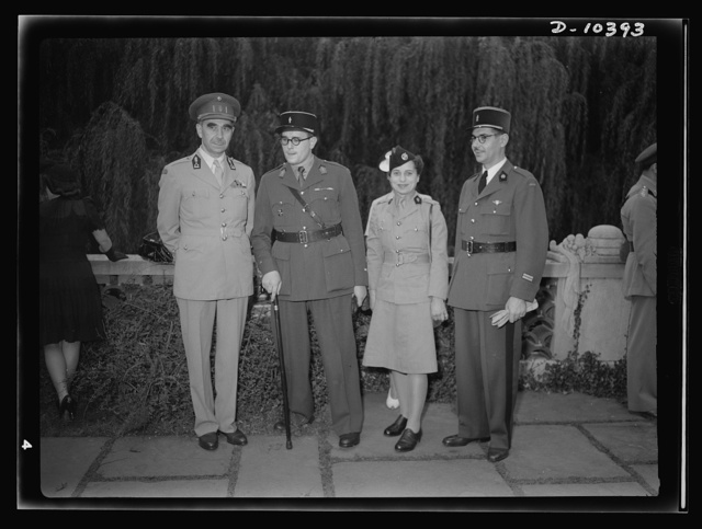 The uniforms are different but the cause is the same. Officers of the United Nations attend a garden party of the United Nations Club at Dumbarton Oaks, Sunday, September 6, 1942. Left to right: Colonel B. E. M. Pierre Diepenryck, Military Attache, Belgium; Adjudant de la Salle, France; Madamoiselle S. L., private in the Volontaires, women's equivalent in the Fighting French of the WAAF or Women's Army Auxiliary Corps (WAAC). This woman has relatives in occupied France and does not want her name mentioned; Lieutenant Dumont, France