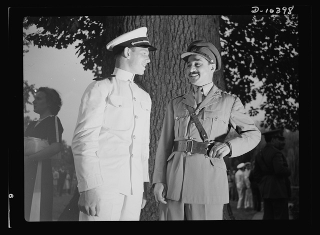 The uniforms are different but the cause is the same. Officers of the United Nations attend a garden party of the United Nations Club at Dumbarton Oaks, Sunday, September 6th, 1942. Left to right: Naval Aviation Cadet John Edward Sinclaire, United States of America and Captain Chaudhuri, Military Aide to the Agent General for India