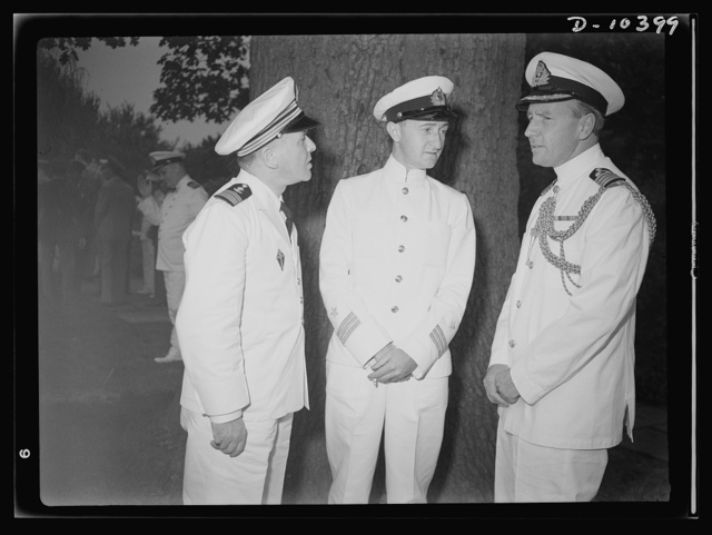 The uniforms are different but the cause is the same. Officers of the United Nations attend a garden party of the United Nations Club at Dumbarton Oaks, Sunday, September 6th, 1942. Left to right: Captain J. G. Gayral, France; Commander Skriagin, Russia; Captain W. Jameson, Assistant Naval Attache, British Embassy