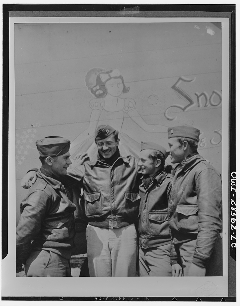 "These four members of the crew of ""Snow White"" a B-24 bomber, of the United States Army Ninth Air Force, have completed 300 hours combat time in the same bomber they brought to the Mediterranean theater from America. Under the protecting wing of Snow White are (left to right) Technical Sergeant John A. Harkell, Captain Rolo C. Lawrence, Sargeant George A. Brunnell and Sergeant Kermit E. Gregory"