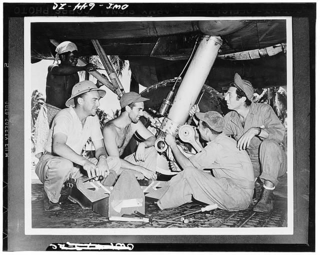 These mechanics servicing a B-17 somewhere in the South Pacific warzone are unsung heroes of the Army Air Force. For every member of the flying crew, there are at least ten ground men who work long hours to keep them flying. Left to right: Sergeant Frank Piotroszer, Hadley, Massachusetts; Corporal William Smith, Woodside, Long Island, New York; Corporal Irvin Andreazza, Weed, Colorado; and Corporal Abe Brodax, Brooklyn, New York