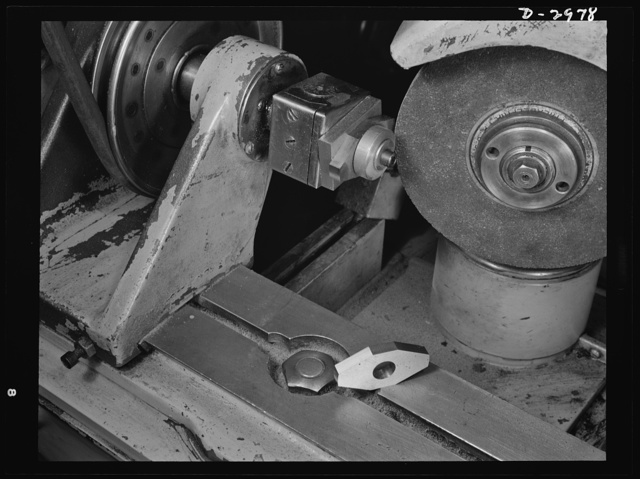 This Norton cutter-grinder which had been specially adapted to grind cams on the motor shaft for the electric dry shaver which this New England plant normally produces, has now been converted to grind permanent magnet rotors for machine tool motors. The conversion was accomplished with new jigs and fixtures and slight changes in the head. This is a tricky job well suited to the skill of this plant's workers. The metal is alnico and the octagonal shape consists of surfaces which are arcs drawn from the center of the piece. Schick Inc., Stamford, Connecticut