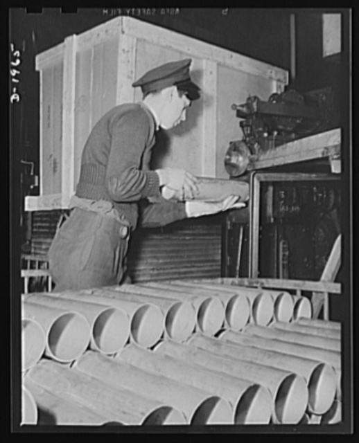 Three-inch A.A. cartridge cases. Beginning as a flat disc, the antiaircraft case is now advanced to a tubular shape of increased length and is nearly ready for the third draw that will lengthen it still more. Before the drawing operation a plant workman gives it a rough trim