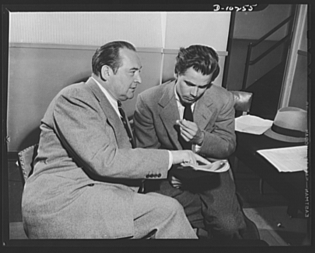 Three Thirds of the Nation. Edward Arnold and Glen Ford, stars on War Production Board (WPB) radio program Steel, presented May 6 over Blue Network, look over script during lull in rehersal