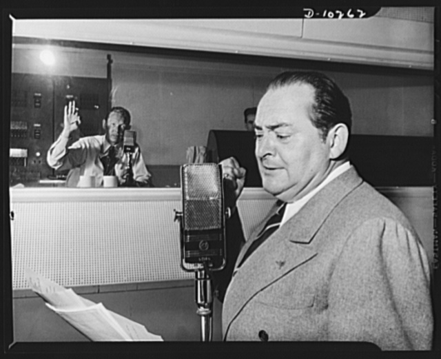 "Three Thirds of the Nation. Edward Arnold hits punch line on the War Production Board (WPB) radio program ""Steel,"" presented over Blue Network on May 6. In background, director Sam Pierce signals Meredith Wilson to come in with music"