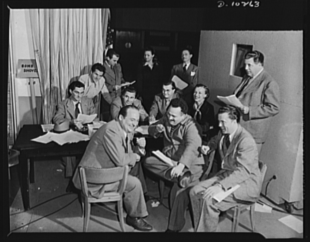 """Three Thirds of the Nation. Here is the cast of the War Production Board (WPB) radio program """"Steel."""" Rehearsal is over and the cast relaxes for a few minutes before going on the air. The actors shown here are Edward Arnold, Howard McNeer, Frank Graham, Fred Shields, Janet Eberhardt, Pat McGeehan, Cy Kendall, Eric Rolf, Lou Merrill, Lucille Meredith, Joe Kearns and Glen Ford"""