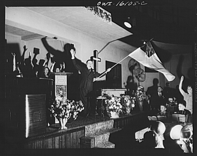 Toledo, Ohio. Evangelical church ceremony at which the preacher delivered a hysterical speech, and then burned a copy of Hitler's Mein Kampf. Preacher waving a church flag while the chorus sings Hallelujah