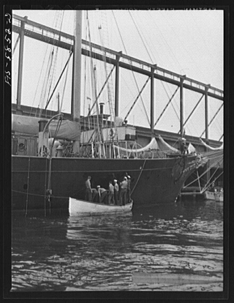Trainees painting the schooner Vema at Pier 18, Staten Island, New York. The Vema was assigned to the nearby merchant marine training center at Hoffman Island