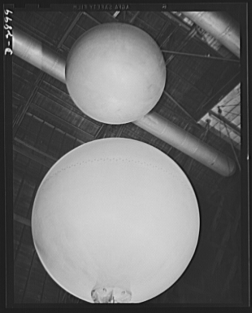 """Transformer manufacture. These huge aluminum spheres are used to test each power transformer which is ready to be shipped from a large Eastern electrical plant. Since lightning is apt to destroy power units in the field, each transformer is given an """"artificial lightning"""" test to determine its ability to resist the elements. These spheres are part of a setup that produces 2,500,000 volts for testing purposes. Westinghouse, Sharon, Pennsylvania"""