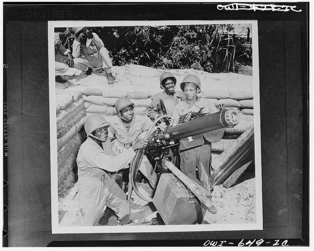 Troops at a U.S. Army airbase in New Hebrides manning a heavy machine gun. Left to right: Private First Class Elliott Moore, Trenton, New Jersey; Corporal Raymond Elliott, Jaspar, Alabama; Corporal Johnny Jackson, Augusta, Georgia; Private First Class Shade Mackee, Jr., Ashland, Alabama