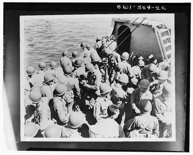 Troops of the Army Task Force, enroute from New Caledonia to the Solomon Islands, checking their rifles and preparing for inspection. They are wearing the new-type U.S. Army helmet