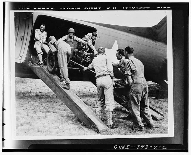 Troops of the U.S. Airbourne Infantry loading a field piece o a transport plane preparatory to taking off in maneuvers in the southwestern United States