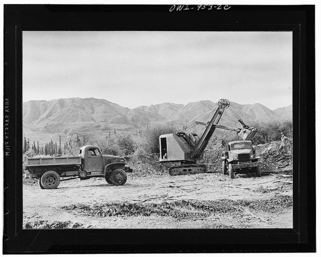 Trucks loading up at the gravel dump. Most of the gravel used for surfacing along the Alcan Highway was obtained from glacial deposits found alongside the roadway
